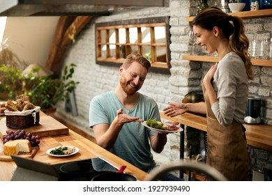 Happy man surprising his girlfriend with a breakfast in the kitchen.