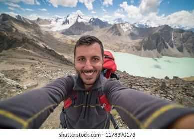 happy man take selfie in Ala Kul lake in Kyrgyzstan, central Asia
