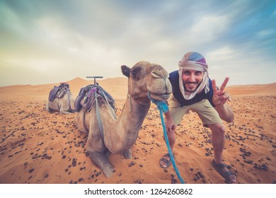 happy man taking crazy selfie with camel in Sahara Desert, Morocco - Immagine