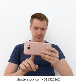 Happy man taking picture with mobile phone and looking to camera while standing against white wall