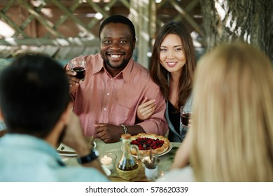 Happy man toasting with red wine by table with his girlfriend near by