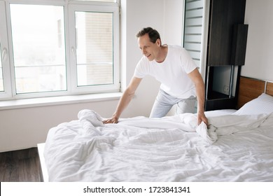 happy man touching white blanket in modern bedroom