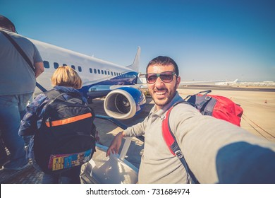 happy man tourist backpacker with sunglasses ready for boarding on plane in airport, summer vacation and travel around the world