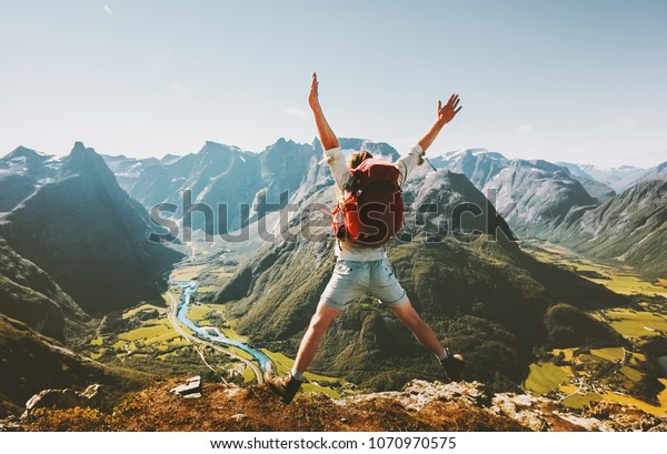 Happy Man traveler jumping with backpack Travel Lifestyle adventure concept active summer vacations outdoor in Norway mountains success and fun euphoria emotions