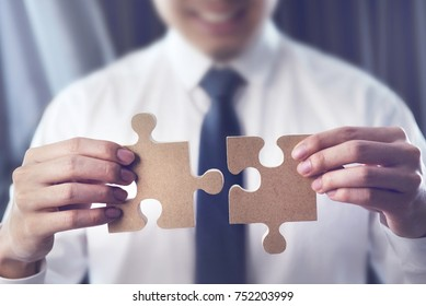 Happy Man is trying to connect couple puzzle piece. Symbol of association and connection. Concept of business strategy.