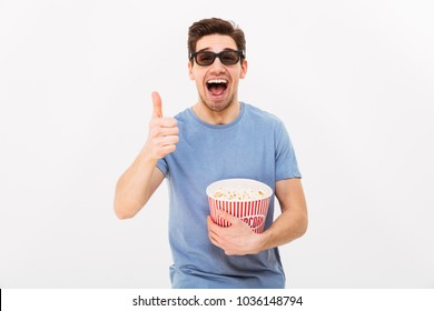 Happy man in t-shirt and 3d glasses holding bucket with popcorn while showing thumb up and looking at the camera over grey background