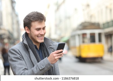 Happy man uses a smart phone walking in a city old town