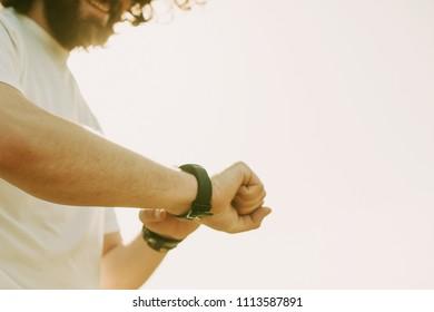 happy man using his smartwatch outdoor