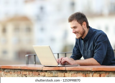 Happy man using a laptop in a rural apartment terrace on vacation