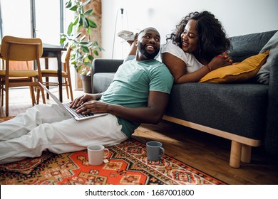 Happy man using a laptop and smiling to a beautiful girlfriend on the sofa