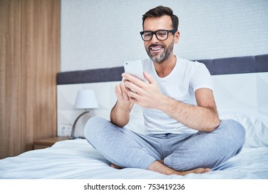 Happy man using phone while sitting on bed
