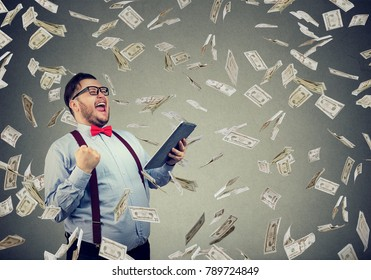 Happy man using tablet and posing with triumph in flying dollar bills.