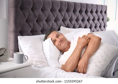 Happy man waking up after sleeping on comfortable pillow in bed at home