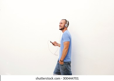 Happy man walking with mobile phone listening to music on headphones