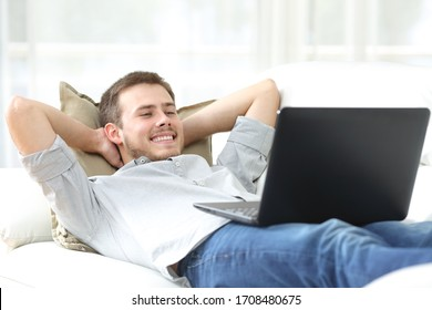 Happy man watching movie streaming online on laptop lying on a couch at home