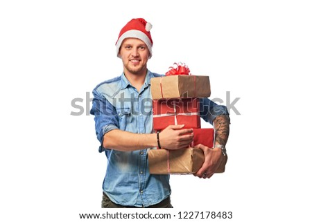 a69c01f5d7bd9 A happy man wearing in a denim shirt and Santa hat holding gifts boxes.