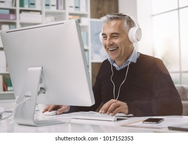 Happy man wearing headphones and watching movies online in his home office, he is enjoying and smiling