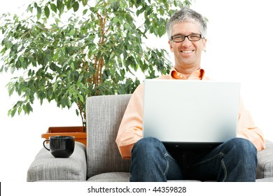 Happy man wearing jeans and orange shirt sitting on couch, browsing internet on laptop computer. Isolated on white.