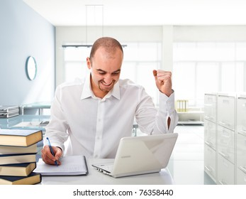 happy man with white laptop in modern office