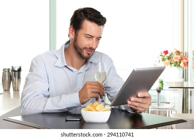 happy man with wine  and tablet at the bar