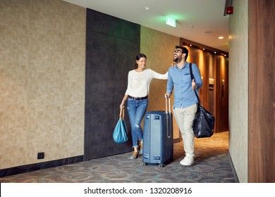 Happy man and woman arriving at hotel lobby with suitcase at vacation
