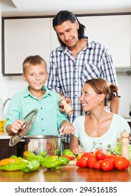 Happy man and woman with boy  adding spices or salt to the pot