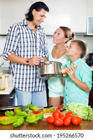 Happy man and woman with boy with fresh vegetables and greens in home kitchen