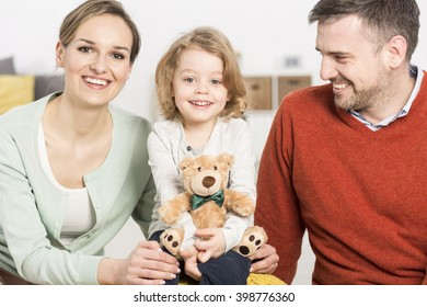 Happy man, woman and child holding teddy bear sitting in light interior