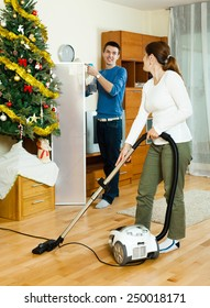 Happy man and woman cleaning with vacuum cleaner in Christmas time