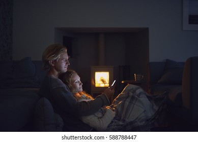 Happy man woman couple using smart phone technology cosy at home by fire connection network romance