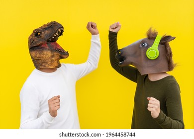 Happy man and woman with dinosaur and horse head mask dancing. Active couple ,positive and celebration people lifestyle, isolated on yellow background in studio with blank wall for copy space .