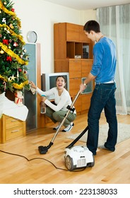 Happy man and woman doing housework together in Christmas time at home