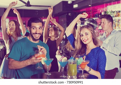 Happy   man with woman are drinking cocktails on corporate party.