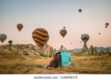 Happy man and woman during sunrise at the rocky landscape in Cappadocia, Turkey. Hot air ballooning in morning is most amazing attraction in Kapadokya during sunrise