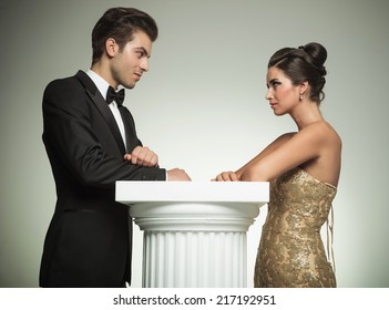 happy man and woman in evening clothes lean on a column and look at each other in studio