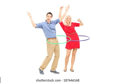 Happy man and woman exercising with hula hoop isolated on white background