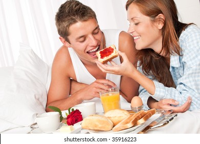 Happy man and woman having luxury hotel breakfast in bed together