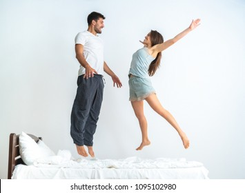 The happy man and a woman jumping on the bed on the white background