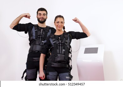 Happy man and woman next to EMS machine, muscle stimulation, showing muscles