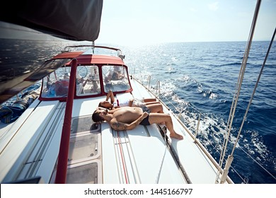 Happy man and woman on boat sunbathing and enjoying on summer day