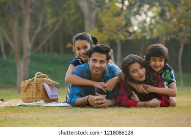 Happy man and woman on a picnic lying down in garden beside a picnic basket and their children lying on their backs