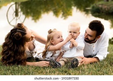 Happy man and woman play with children outside on a sunny day