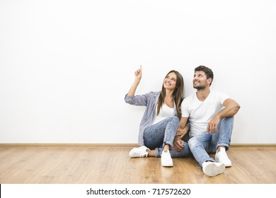 The happy man and woman sit on the background of the white wall