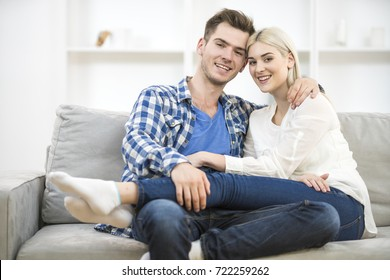 The happy man and woman sit on the sofa