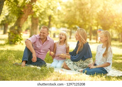 Happy man and woman with smiles playing with children on the street and picnic