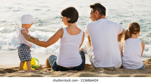 Happy man and woman with two kids sitting with back to camera on sandy beach