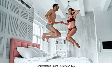 The happy man and woman in underwear jumping on the bed