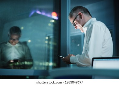 Happy man working overtime in modern office late at night. Mature businessman typing on cell phone, with city lights in background from office window.