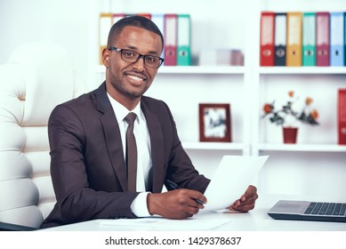 Happy Man at Workplace. African American Businessman Loves Job. Executive is Working in Office at Desk.