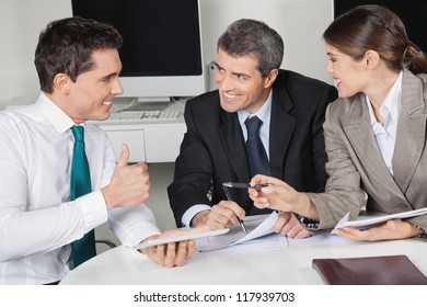 Happy manager in business meeting holding his thumb up